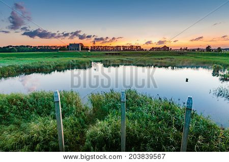 An old harbor head in the dry fallen polder of the Netherlands during sunset and the evening. A foot with contrasting and beautiful light