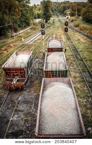 Freight cars with crushed stone on the railroad in summer evening. Top view with semaphores on the background