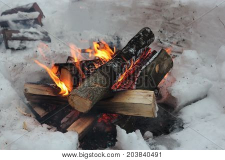 A bonfire on the snow with firewood fire coals and smoke