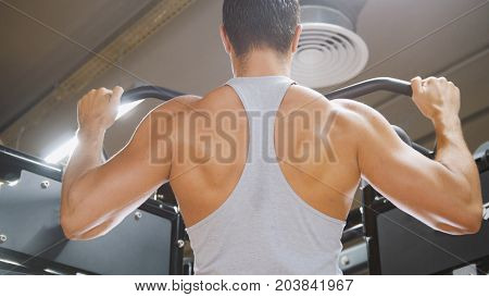 Bodybuilder in the gym performs pull up for back - close up view
