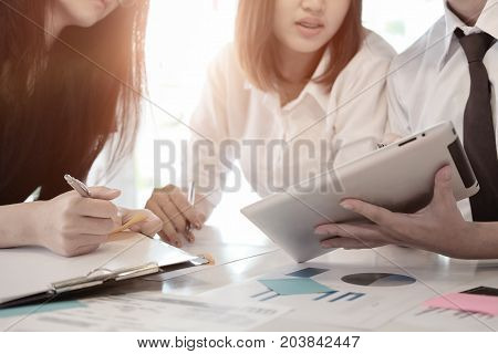Three business partners discussing documents and ideas at meetingbusiness consulting concept.