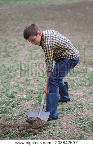 Young guy is digging the earth autumn in the park. The boy is digging soil with a shovel at spring green outdoors background. Young boy, big shovel, autumn day.