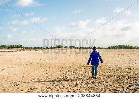 Woman in a blue jacket walks into a nature area with lots of sand. It's a sunny day in summer.