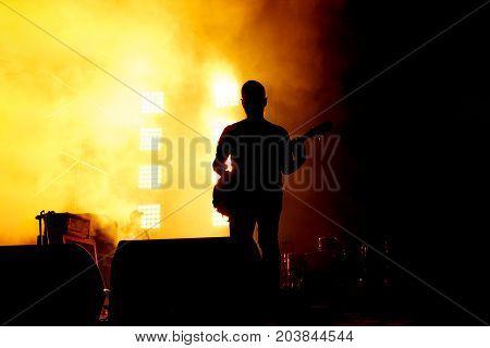 Elegant guitarist silhouette on stage. Orange background, smoke, concert spotlights
