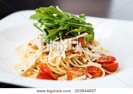 Classical chicken pasta with ruccola, tomatoes and cheese