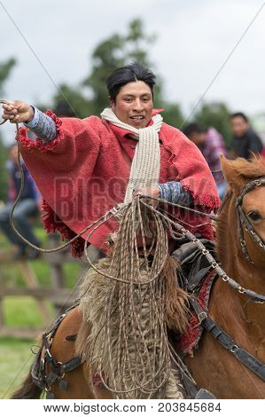 June 3 2017 Machachi Ecuador: closeup of indigenous quechua cowboy in motion on horseback dressed traditionally handling lasso on horseback