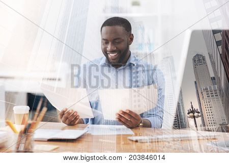 Comparing information. Close up of smiling intelligent worker holding documents and comparing information while showing interest to his work