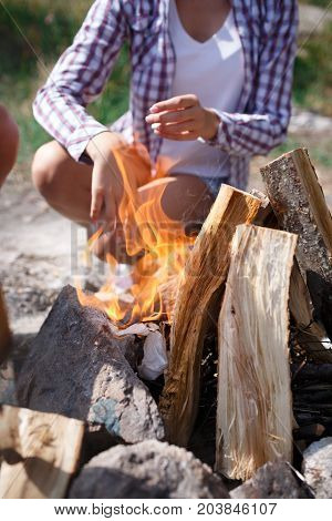 A girl in a plaid shirt throws paper into the fire to fry the meat. Preparation of a campfire for a summer picnic in the open air. Enjoy your time outdoors in summer. Beautiful fire in the forest.