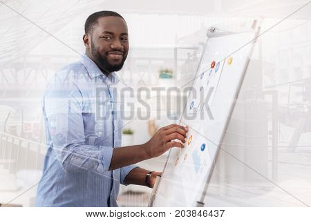 Endless energy. Waist up of cheerful enthusiastic African American working with magnet board and looking at you with a cheerful smile