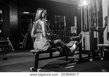 Young blonde Woman training back with weight-lifting training machine