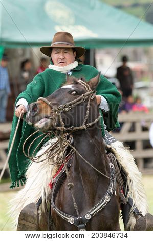 June 3 2017 Machachi Ecuador: closeup of Andean cowboy on horseback dressed traditionally holding leather lasso on horseback