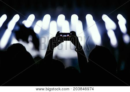 Video recording of the concert on the phone a smartphone. Back silhouette of hands