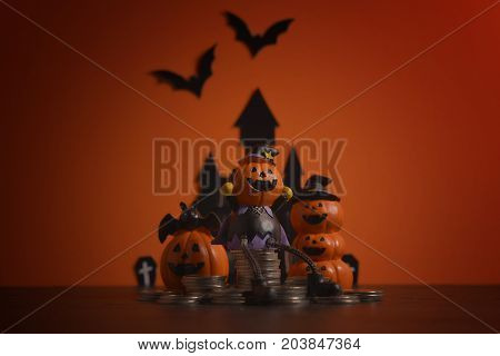 Halloween pumpkins jack-o-lantern with money coin stack growing business on orange background. Halloween pumpkin background. Halloween. jack-o-lantern. Halloween jack-o-lantern. Happy Halloween.