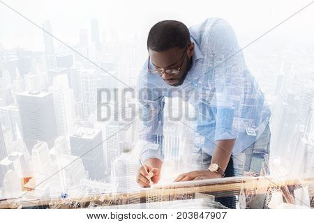 Smart approach. Attentive young African American working on new project while standing completely involved in the process