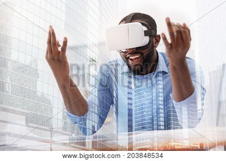 Funny meditation. Close up of African American wearing mask on his face while putting elbows on the table