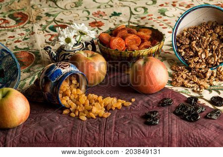 dried fruit in cups on an oriental ornamented tablecloth. still life in oriental style