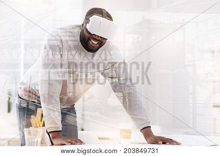 Working tools. Close up of smiling African American with a white mask on his head while leaning on the table and looking at you with admiration
