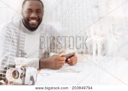Instrument for working. Close up of expensive white mask lying on the table while smiling African American using a mobile phone