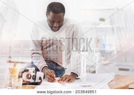Dedicated to job. Waist up of smiling engineer sitting on the table while working with the sketches expressing interest