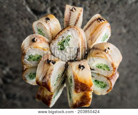 Roll with smoked eel, cream cheese and cucumber over concrete background