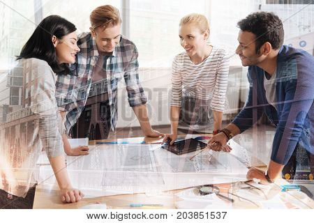 Successful collaboration. Waist up of smart enthusiastic coworkers discussing a new project while standing around the table and expressing interest