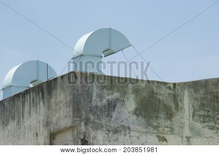 Blue air duct With a bare cement wall With blue sky