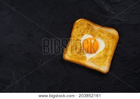 Heart shaped fried egg baked in a toast. Tasty breakfast for Valentines day on black background. Space for text