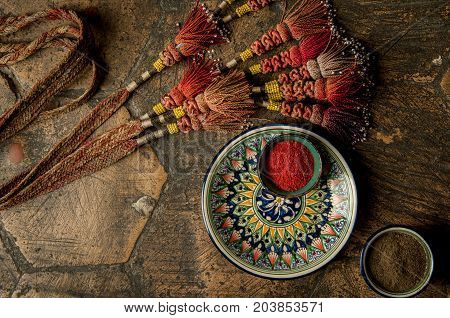 oriental spices in cups and decorated adorned with a whip on an old worn paving stone. oriental spices and decorations on decorative old tiles