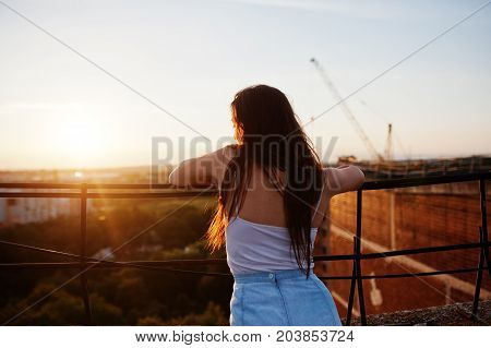 Portrait Of A Gorgeous Young Woman In Casual Clothing Admiring The Sunset From The Roof Of A Buildin