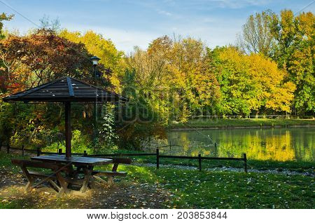 Picnic table by the lake surrounded by the forest in autumn colors, Belgrade, Serbia