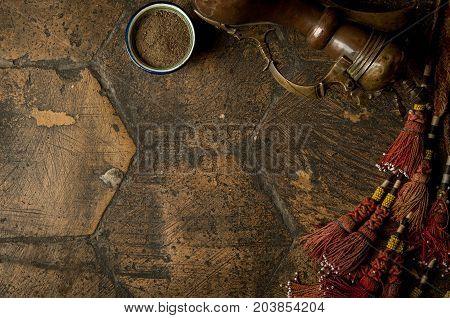 east spices with a copper jug and decorative whip on an old worn paving stone. oriental spices and a copper jug on a decorative old tile