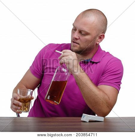 A troubled man in a crimson T-shirt is holding a big bottle and a transparent glass full of cognac, isolated on a white background. A sad boozed guy with an alcoholic drink on a wooden table.