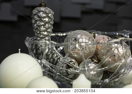 Christmas decorations of globular candles and vases with Christmas toys on a dark background with tiles