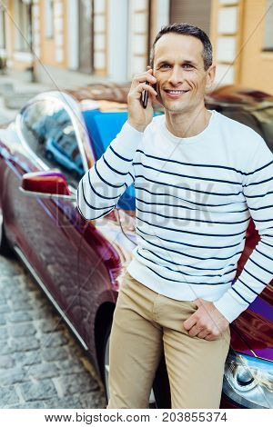 Mobile connection. Positive delighted nice man smiling and putting a cell phone to his ear and talking while standing near his car