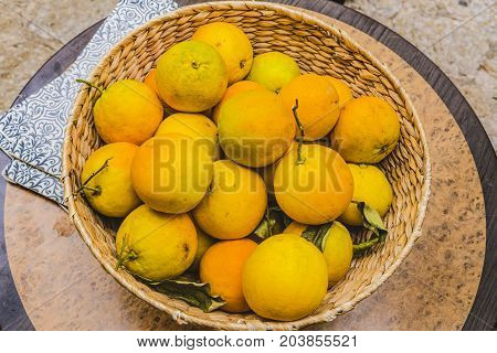 a wicker basket with organic oranges .