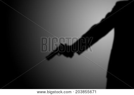 Killer shooting a gun. black and white. robbery, murder, crime and security concept