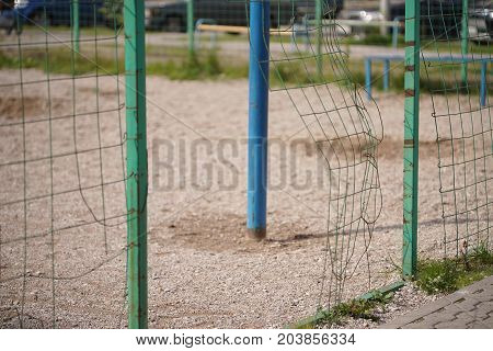Broken steel mesh of metal fence of a basketball court in residential neighborhood in summer