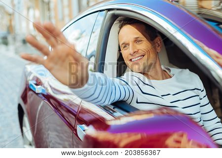 Saying hello. Joyful nice pleasant man smiling and waving from his car window while sitting in his car