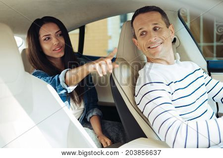 We need to go there. Nice pleasant beautiful woman sitting on the back seat and pointing with her finger while telling the driver where to go