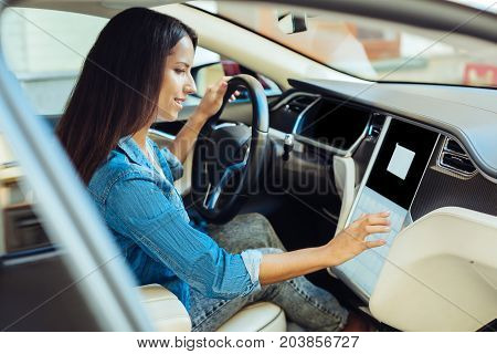 Female driver. Nice pleasant delighted woman sitting behind the heel of her car and pressing a sensory button while starting the engine
