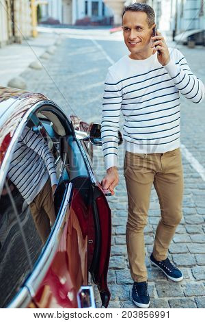 Into the car. Positive nice good looking man holding the car door and talking on the phone while getting inside