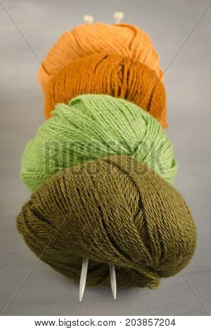 Orange brown green and marsh woolen yarn and knitting needles on a gray background