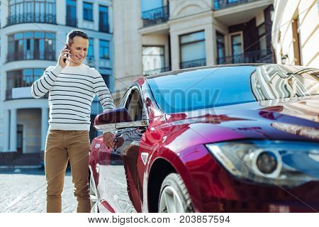 Car owner. Cheerful nice pleasant man standing on the street and opening the door of his car while talking on the phone