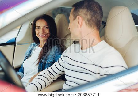 I am ready to go. Nice beautiful positive woman sitting on the passenger seat and smiling while looking at her boyfriend