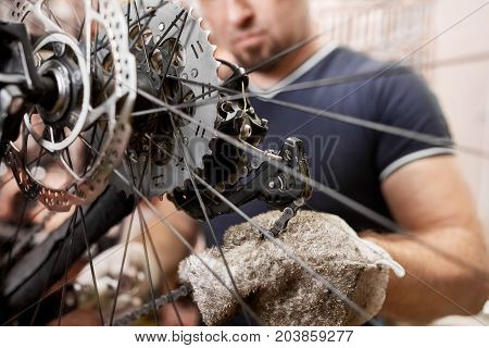 Bicycle mechanic in a workshop in the repair process. Man repair his bike.