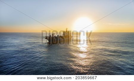 GOLD COAST, AUSTRALIA - SEPTEMBER 10 2017: Balder R Hopper Dredger on the open sea's silhouette at sunrise.