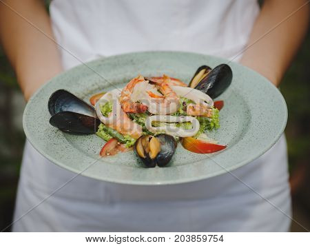Fresh shrimp, mussel, tomat, salad leaf. Beautiful dish on a large light plate. Professional, seasonal kitchen. Exotic dish in an expensive restaurant. A plate on the hands.
