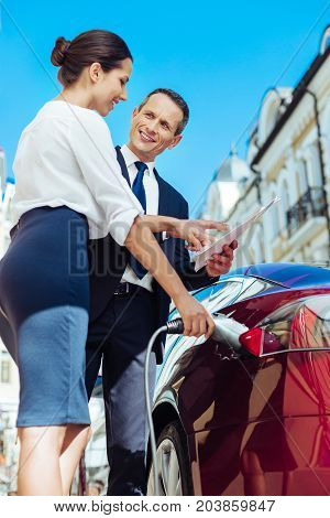 Work everywhere. Delighted nice handsome businessman holding a document and showing it to his business partner while standing near the car