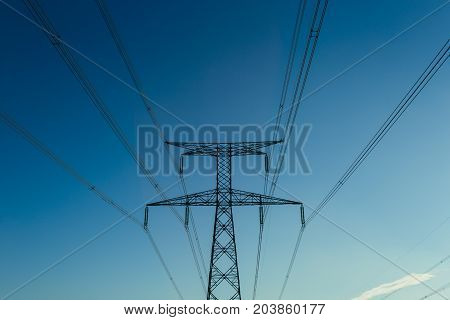 High Voltage Power Lines And Transmission Towers On A Bright Sunny Day In Normandy, France. Electric