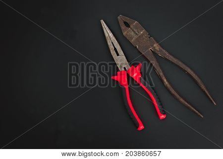 Must have at home used hand tools Combination Pliers and Needle Nose Pliers on black background with copy space
